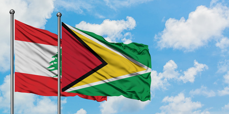 Lebanon and Guyana flag waving in the wind against white cloudy blue sky together. Diplomacy concept, international relations.