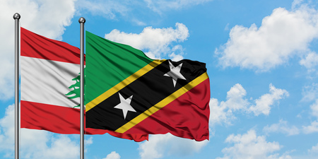 Lebanon and Saint Kitts And Nevis flag waving in the wind against white cloudy blue sky together. Diplomacy concept, international relations.