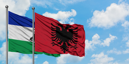 Lesotho and Albania flag waving in the wind against white cloudy blue sky together. Diplomacy concept, international relations.