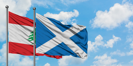 Lebanon and Scotland flag waving in the wind against white cloudy blue sky together. Diplomacy concept, international relations.