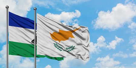 Lesotho and Cyprus flag waving in the wind against white cloudy blue sky together. Diplomacy concept, international relations. Banco de Imagens