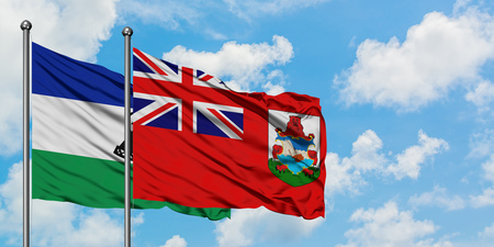 Lesotho and Bermuda flag waving in the wind against white cloudy blue sky together. Diplomacy concept, international relations.