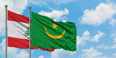 Lebanon and Mauritania flag waving in the wind against white cloudy blue sky together. Diplomacy concept, international relations. Banco de Imagens