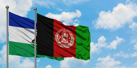 Lesotho and Afghanistan flag waving in the wind against white cloudy blue sky together. Diplomacy concept, international relations.