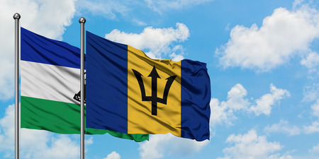 Lesotho and Barbados flag waving in the wind against white cloudy blue sky together. Diplomacy concept, international relations.
