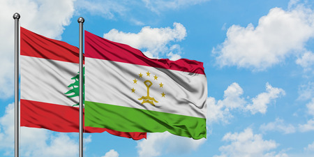 Lebanon and Tajikistan flag waving in the wind against white cloudy blue sky together. Diplomacy concept, international relations. Banco de Imagens