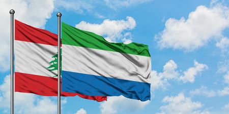 Líbano y Sierra Leona bandera ondeando en el viento contra el cielo azul nublado blanco juntos. Concepto de diplomacia, relaciones internacionales.