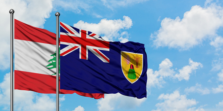 Lebanon and Turks And Caicos Islands flag waving in the wind against white cloudy blue sky together. Diplomacy concept, international relations.