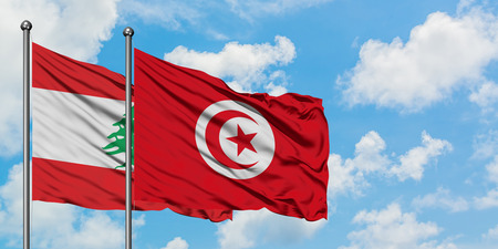 Lebanon and Tunisia flag waving in the wind against white cloudy blue sky together. Diplomacy concept, international relations.