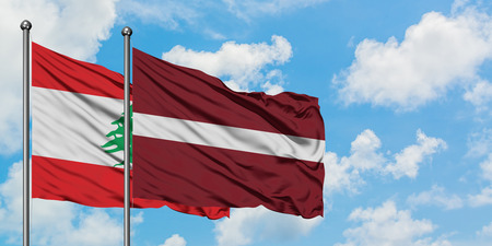 Lebanon and Latvia flag waving in the wind against white cloudy blue sky together. Diplomacy concept, international relations. Banco de Imagens