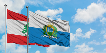 Lebanon and San Marino flag waving in the wind against white cloudy blue sky together. Diplomacy concept, international relations.