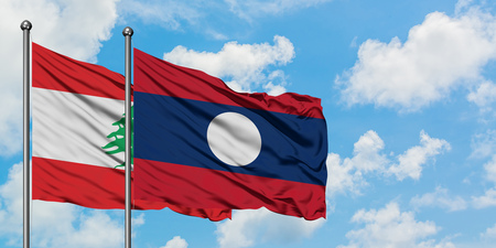 Lebanon and Laos flag waving in the wind against white cloudy blue sky together. Diplomacy concept, international relations.