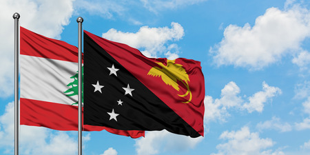 Lebanon and Papua New Guinea flag waving in the wind against white cloudy blue sky together. Diplomacy concept, international relations. Banco de Imagens