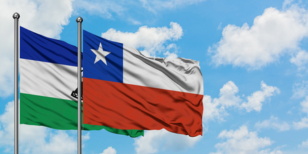 Lesotho and Chile flag waving in the wind against white cloudy blue sky together. Diplomacy concept, international relations.