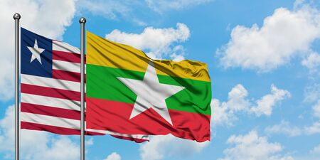 Liberia and Myanmar flag waving in the wind against white cloudy blue sky together. Diplomacy concept, international relations.