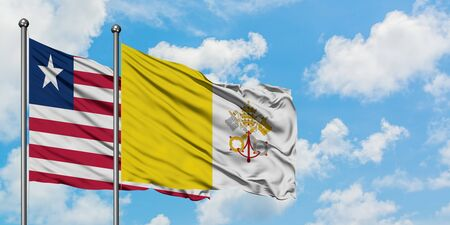Liberia and Vatican City flag waving in the wind against white cloudy blue sky together. Diplomacy concept, international relations.
