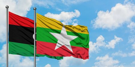 Libya and Myanmar flag waving in the wind against white cloudy blue sky together. Diplomacy concept, international relations.