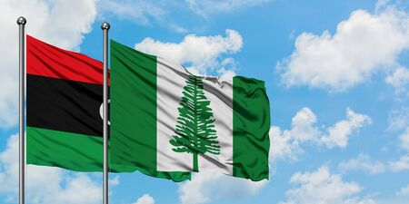 Libya and Norfolk Island flag waving in the wind against white cloudy blue sky together. Diplomacy concept, international relations.