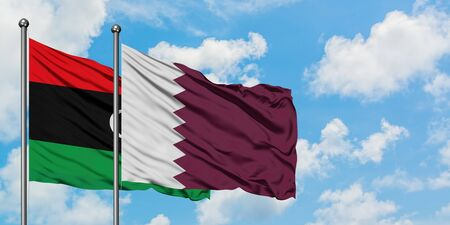 Libya and Qatar flag waving in the wind against white cloudy blue sky together. Diplomacy concept, international relations.