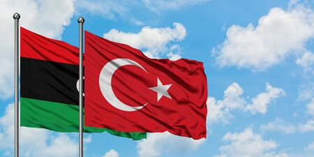 Libya and Turkey flag waving in the wind against white cloudy blue sky together. Diplomacy concept, international relations.