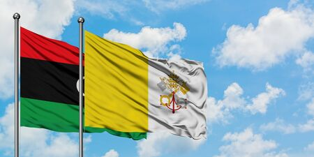 Libya and Vatican City flag waving in the wind against white cloudy blue sky together. Diplomacy concept, international relations.
