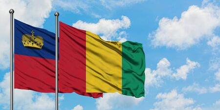 Liechtenstein and Guinea flag waving in the wind against white cloudy blue sky together. Diplomacy concept, international relations.
