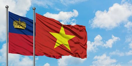 Liechtenstein and Vietnam flag waving in the wind against white cloudy blue sky together. Diplomacy concept, international relations.