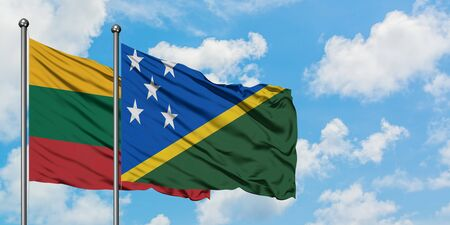 Lithuania and Solomon Islands flag waving in the wind against white cloudy blue sky together. Diplomacy concept, international relations.