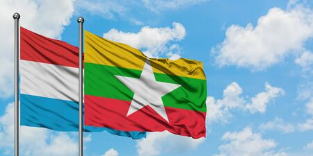 Luxembourg and Myanmar flag waving in the wind against white cloudy blue sky together. Diplomacy concept, international relations. Stok Fotoğraf