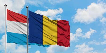 Luxembourg and Romania flag waving in the wind against white cloudy blue sky together. Diplomacy concept, international relations.
