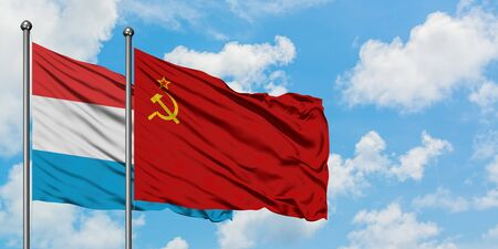 Luxembourg and Soviet Union flag waving in the wind against white cloudy blue sky together. Diplomacy concept, international relations.