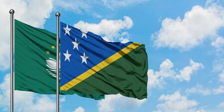 Macao and Solomon Islands flag waving in the wind against white cloudy blue sky together. Diplomacy concept, international relations.