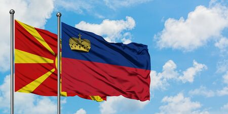 Macedonia and Liechtenstein flag waving in the wind against white cloudy blue sky together. Diplomacy concept, international relations.