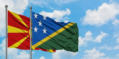 Macedonia and Solomon Islands flag waving in the wind against white cloudy blue sky together. Diplomacy concept, international relations.