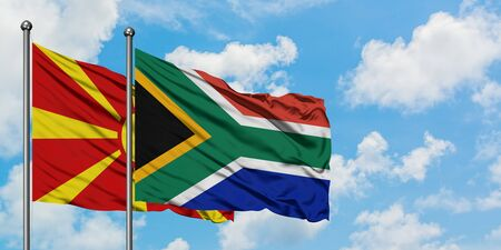 Macedonia and South Africa flag waving in the wind against white cloudy blue sky together. Diplomacy concept, international relations.