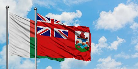 Madagascar and Bermuda flag waving in the wind against white cloudy blue sky together. Diplomacy concept, international relations.