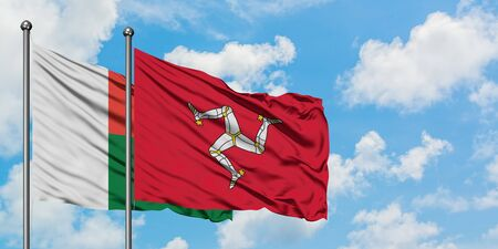 Madagascar and Isle Of Man flag waving in the wind against white cloudy blue sky together. Diplomacy concept, international relations.