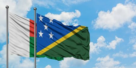 Madagascar and Solomon Islands flag waving in the wind against white cloudy blue sky together. Diplomacy concept, international relations.