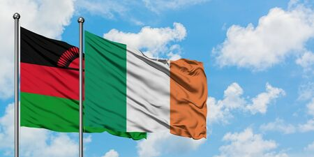 Malawi and Ireland flag waving in the wind against white cloudy blue sky together. Diplomacy concept, international relations.