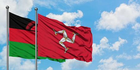 Malawi and Isle Of Man flag waving in the wind against white cloudy blue sky together. Diplomacy concept, international relations. Banque d'images