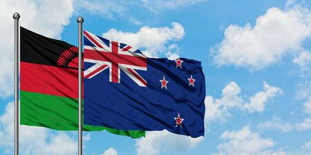 Malawi and New Zealand flag waving in the wind against white cloudy blue sky together. Diplomacy concept, international relations.