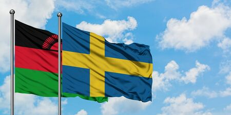 Malawi and Sweden flag waving in the wind against white cloudy blue sky together. Diplomacy concept, international relations. Standard-Bild