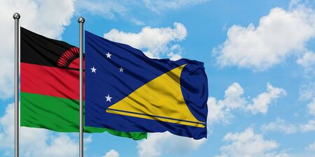 Malawi and Tokelau flag waving in the wind against white cloudy blue sky together. Diplomacy concept, international relations.