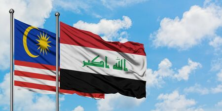 Malaysia and Iraq flag waving in the wind against white cloudy blue sky together. Diplomacy concept, international relations.