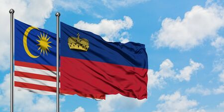 Malaysia and Liechtenstein flag waving in the wind against white cloudy blue sky together. Diplomacy concept, international relations.