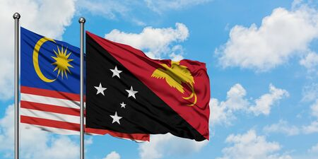 Malaysia and Papua New Guinea flag waving in the wind against white cloudy blue sky together. Diplomacy concept, international relations. Foto de archivo