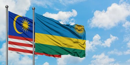 Malaysia and Rwanda flag waving in the wind against white cloudy blue sky together. Diplomacy concept, international relations. Archivio Fotografico