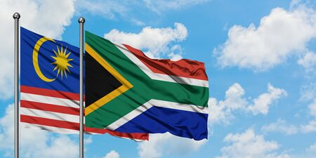 Malaysia and South Africa flag waving in the wind against white cloudy blue sky together. Diplomacy concept, international relations. 스톡 콘텐츠