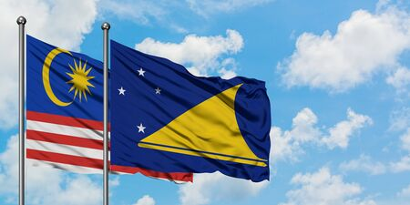 Malaysia and Tokelau flag waving in the wind against white cloudy blue sky together. Diplomacy concept, international relations.
