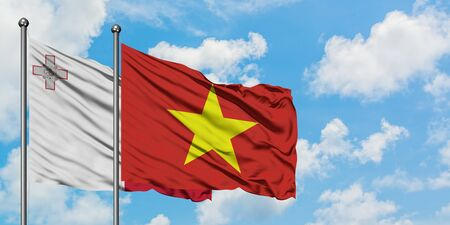 Malta and Vietnam flag waving in the wind against white cloudy blue sky together. Diplomacy concept, international relations.